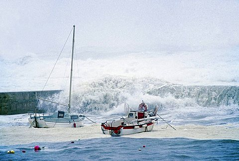 High waves crashing over the harbor wall and small boats, stormy seas on the Brittany coast, hurricane, Finistere, Brittany, France, Europe