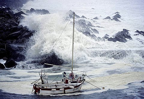 High waves crashing over rocks, rocking small boats, stormy seas on the Brittany coast, hurricane, Finistere, Brittany, France, Europe