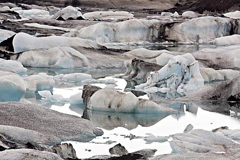 Icebergs in the Joekulsarlon glacial lake with different colorations due to volcanic ash, Joekulsarlon, Vatnajoekull, Iceland, Europe