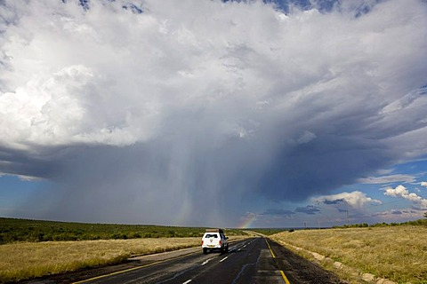 Four-wheel vehicle with a roof tent driving on the Trans Kalahari Highway towards a rainbow, paved road in Namibia, Africa