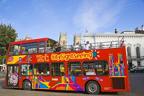 York CitySightseeing, tourist bus, against medieval York with York Minster in the back, Yorkshire, England, United Kingdom, Europe