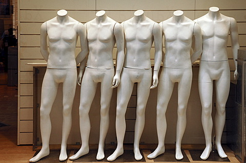 Five naked white mannequins in a fashion store