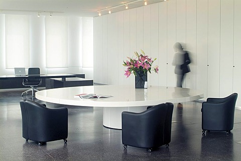 Round white conference table with empty, blue leather chairs and passing secretary