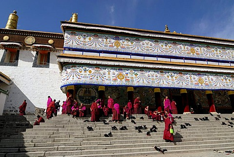 Tibetan monks in cowls of the Gelukpa order sitting on the stairs of the Assembly Hall, Tibetan Dukhang, Labrang Monastery, Xiahe, Gansu, China, Asia