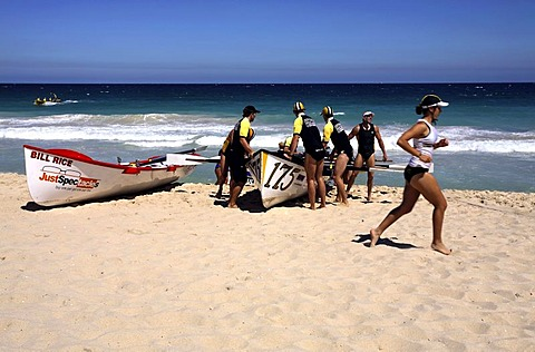 Competition Surf boats and a female Surf Life Saver running on, Scarborough Beach, Perth, Western Australia, Australia