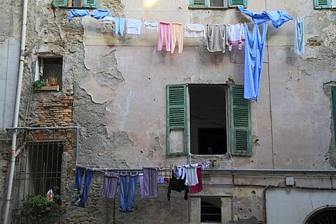 Facade of a house in need of renovation with laundry hanging to dry in the historic town centre of Ventimiglia, province of Imperia, Liguria region, Riviera dei Fiori, Mediterranean Sea, Italy, Europe