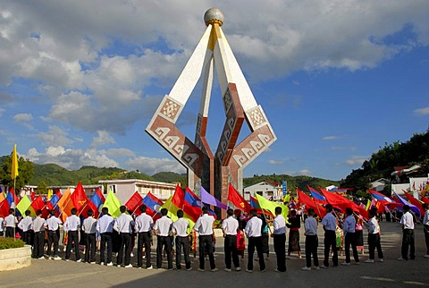 Parade, flag-bearers, young men of the Laotian Youth Organization Lao Youth with many colorful flags standing around a communist monuments, Xam Neua, Houaphan province, Laos, Southeast Asia, Asia