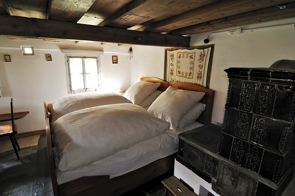 Bedroom with tiled stove, Glentleiten farming museum, Bavaria, Germany, Europe