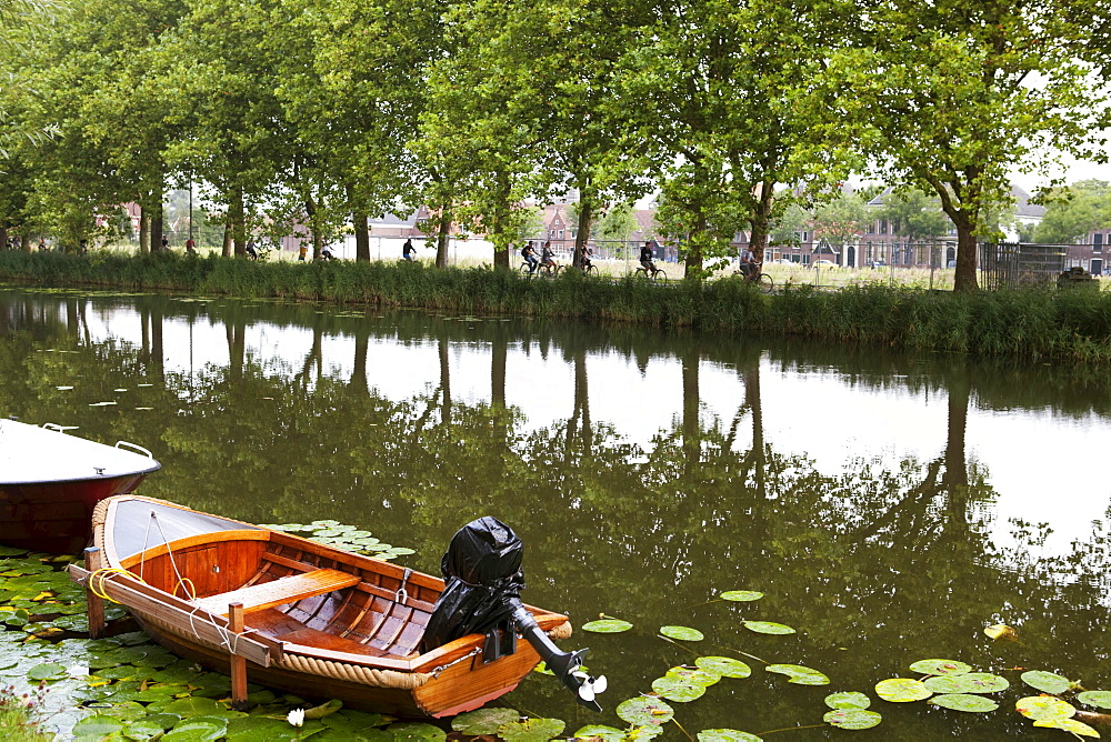 Canal with trees reflected in the water, tourists riding bicycles and small boat, Edam, Holland, Netherlands, Europe