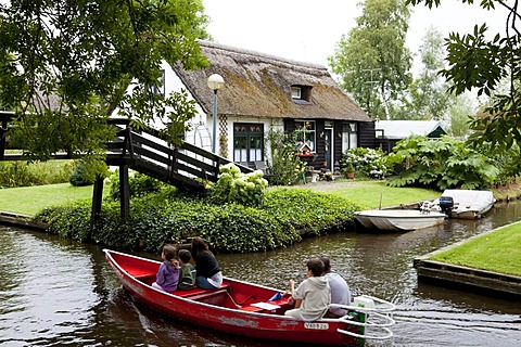 Traditional Dutch housing with garden beside the canal, tourists on a red boat visiting the village, Giethoorn, Flevoland, Netherlands, Europe