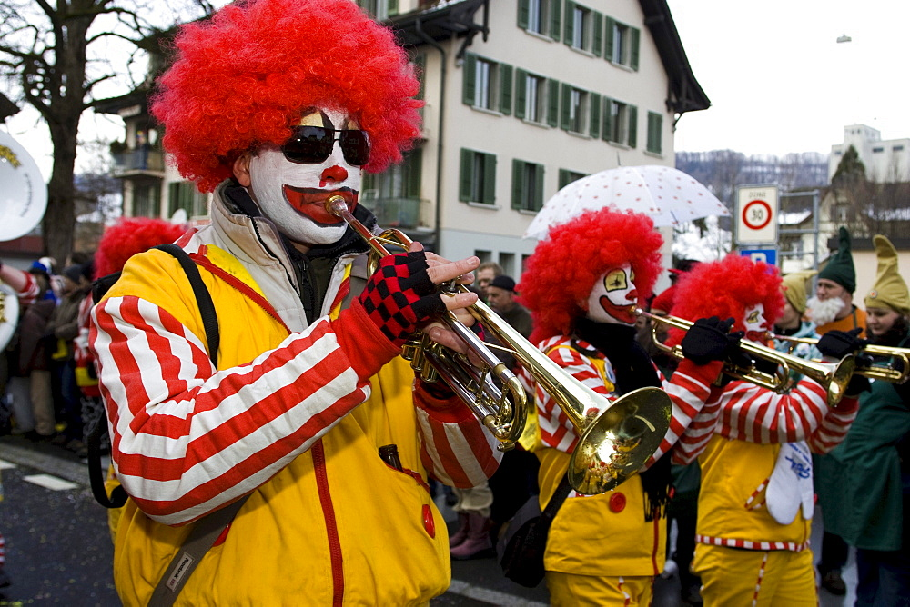 Clown playing the trumpet at the carnival parade in Malters, Lucerne, Switzerland, Europe