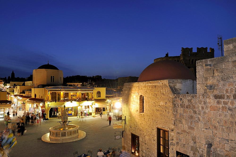 Fountain and Odos Sokratous, a shopping street, seen from Platia Ippokratou, Rhodes Town, Rhodes, Greece, Europe