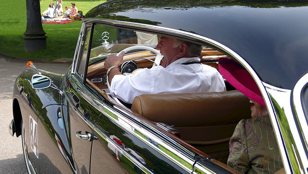Chauffeur and elegant old lady with a pink hat in an old Mercedes Benz 300D