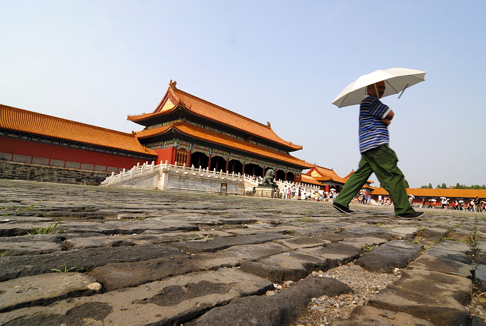 Man with parasol walking over cobblestones, Forbidden City, Imperial Palace, Beijing, China, Asia