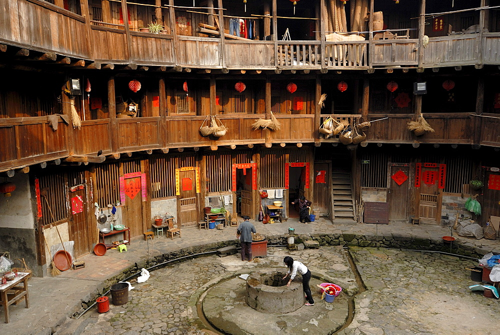 Chinese woman drawing water from the well in the courtyard of a wooden round house, Chinese: Tulou, adobe round house of the Hakka minority, Tianluokeng Building Group, Hukeng, Fujian, China, Asia