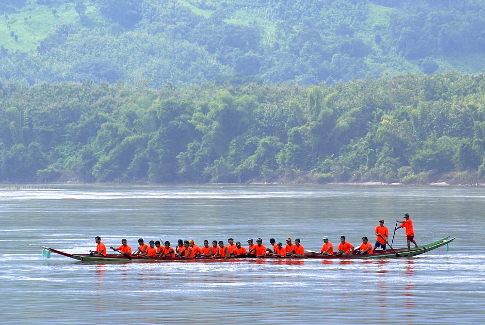 Dragon boat with a great team in orange t-shirts at the dragon boat race on the Nam Ou River, Luang Prabang, Northern Laos, Laos, Southeast Asia