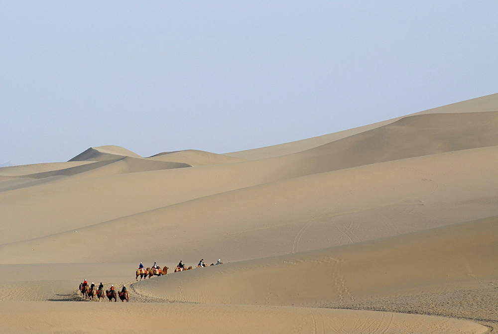 Camel caravan with tourists in front of the sand dunes of the Gobi Desert during the ascent of Mount Mingshan near Dunhuang, Silk Road, Gansu, China, Asia