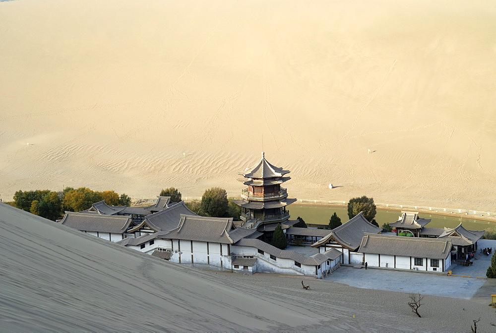 View from the sand dunes of the Gobi Desert to the Crescent Lake with a Chinese pagoda near Dunhuang, Silk Road, Gansu, China, Asia