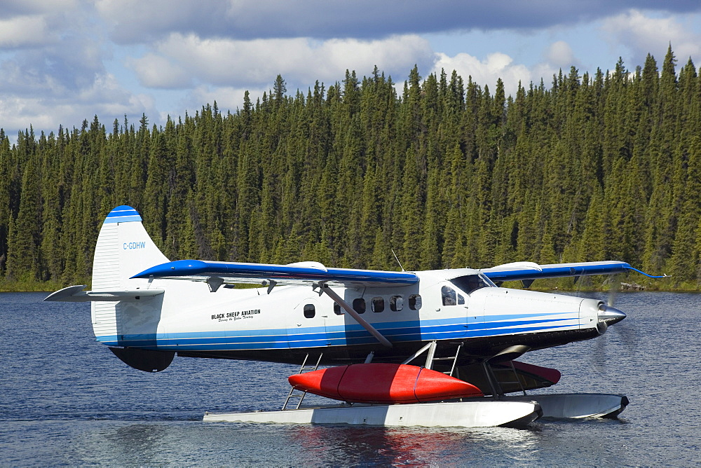 Taxiing de Havilland Canada DHC-3 Otter, Floatplane, Canoe tied to float, bush plane, Caribou Lakes, upper Liard River, Yukon Territory, Canada