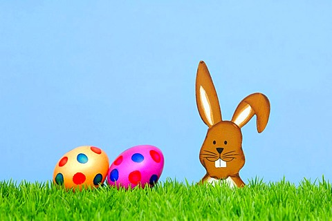 Wooden Easter bunny with coloured Easter eggs, garden decoration, symbolic image for Easter
