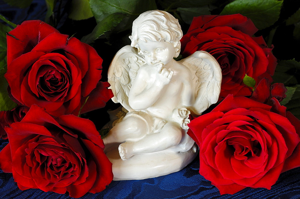 Ceramic angel figurine with red roses