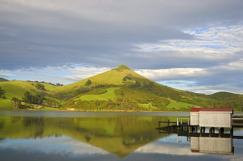 A boathouse and its reflexion in Hoopers Inlet with Harbour Cone at back on the Otago Peninsula, New Zealand