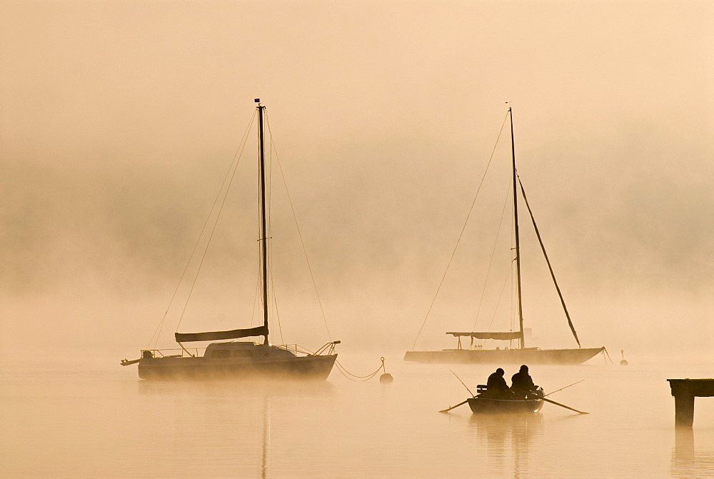 Sailing boats and fog at the southern end of Ammersee lake in Diessen, Bavaria, Germany, Europe
