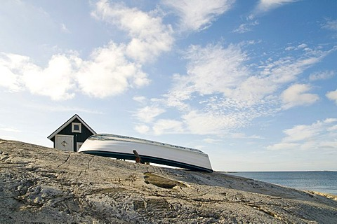 Wooden shed and boat on the rocky coast, Smoegen, Bohuslaen, Sweden