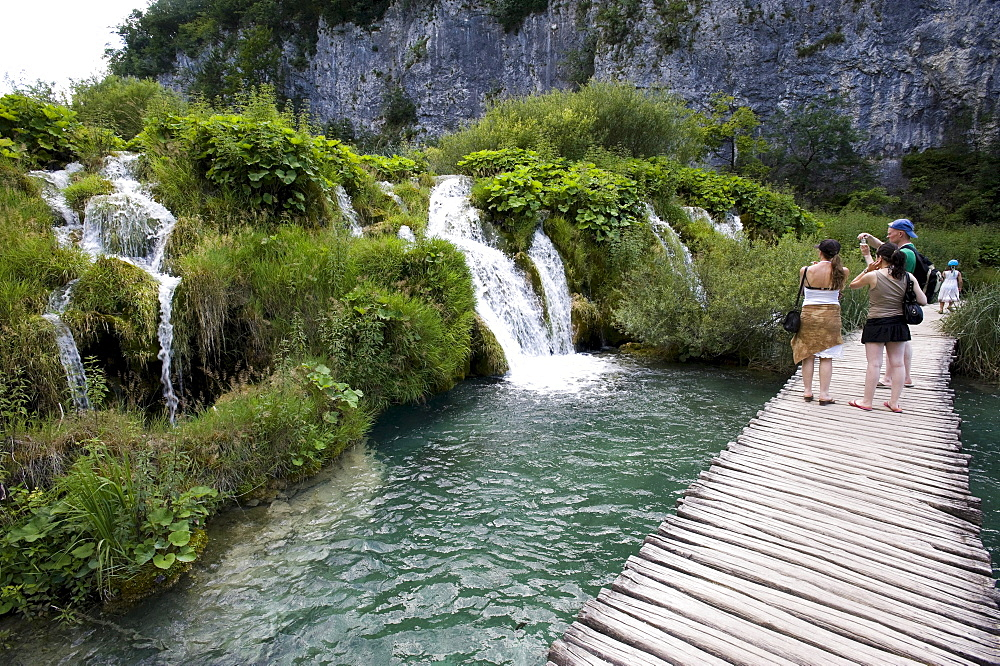 Tourists in front of a small waterfall in the cascade landscape of the Plitvice Lakes, Plitvice Lakes National Park, Croatia, Europe