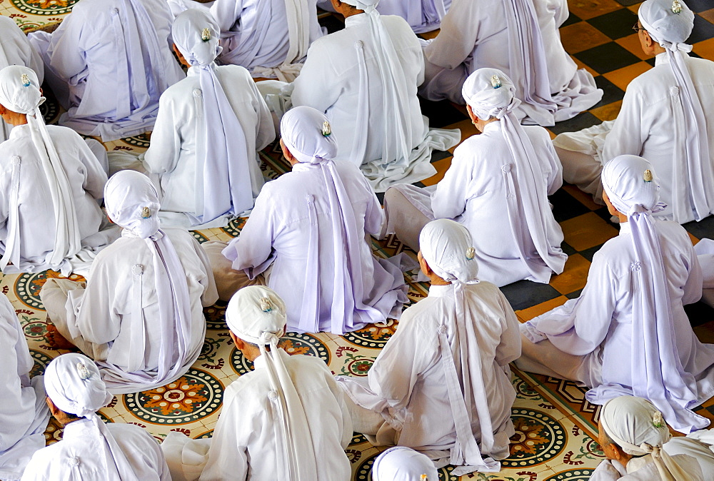 Seated Nuns praying, ceremonial midday prayer in the Cao Dai temple, Tay Ninh, Vietnam, Asia