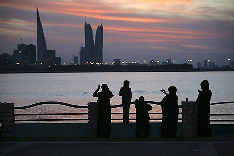Skyline of the Corniche as seen from King Faisal Highway, Muharraq side, World Trade Center buildings, left, beside the towers of the Financial Harbour Complex, pedestrians walking along the Corniche in the evening, capital city, Manama, Kingdom of Bahrai