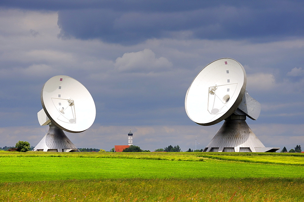 Parabolic antennas at the Erdfunkstelle, station for radio, television and data communications, with the spire of St. Remigius Church in Raisting, district of Weilheim-Schongau, Bavaria, Germany, Europe