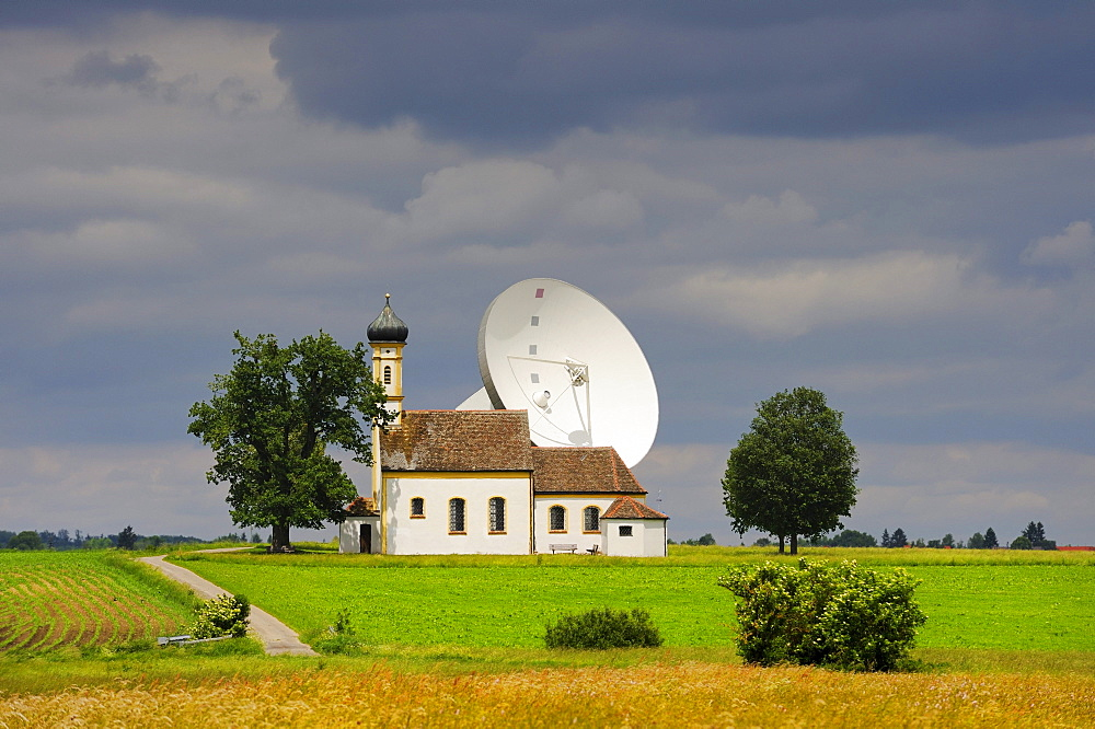 Parabolic antenna at the Erdfunkstelle, station for radio, television and data communications, with a chapel near Raisting, district of Weilheim-Schongau, Bavaria, Germany, Europe