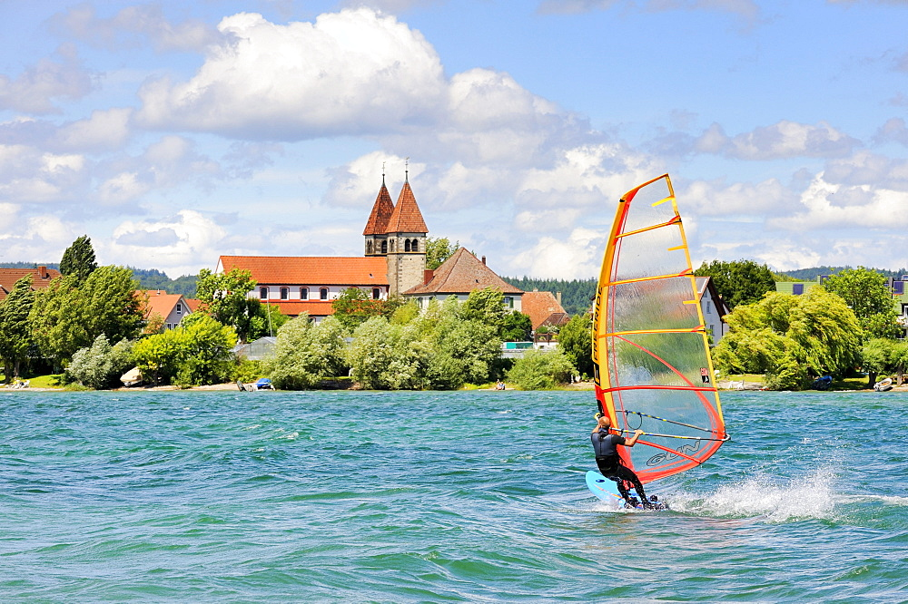 Windsurfer on Lake Constance, shore of Reichenau Island in the back, St. Peter and St. Paul Church, County of Constance, Baden-Wuerttemberg, Germany, Europe