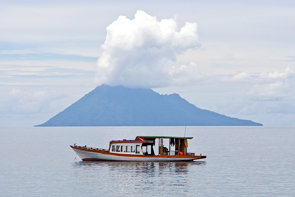 Diving boat in the Bunaken Marine Park in front of Mt Manado Tua, North Sulawesi, Indonesia
