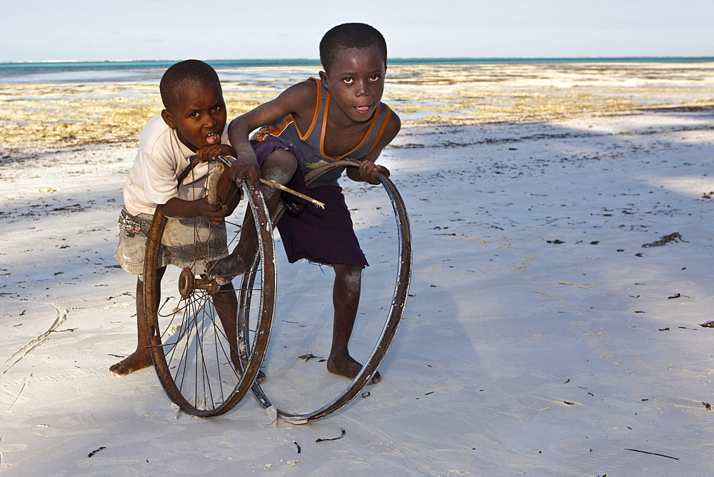 Children playing with old bicycle wheels on the beach of Pingwe, Zanzibar, Tanzania, Africa