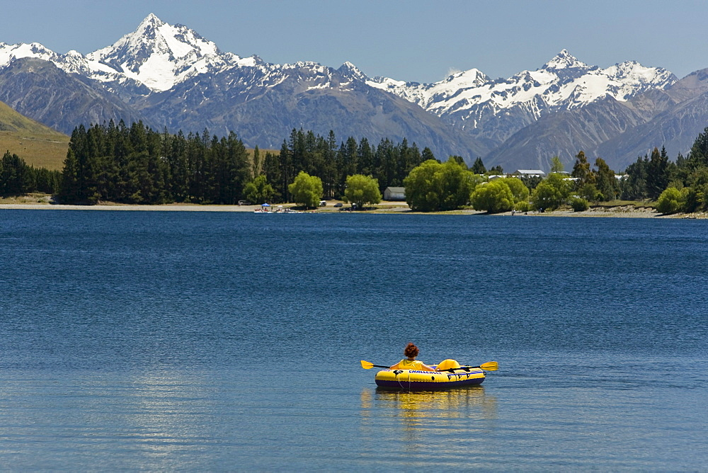 Inflatable boat on Lake Camp with views of the mountains of Cloudy Peak Range, South Island, New Zealand