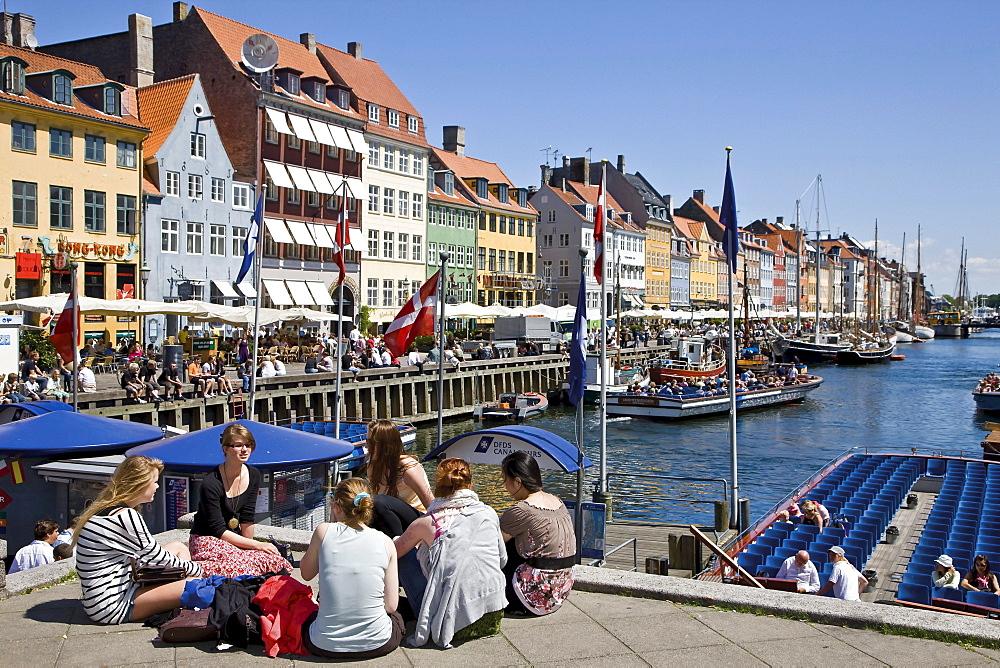 Tourists relaxing in Nyhavn, Copenhagen, Denmark