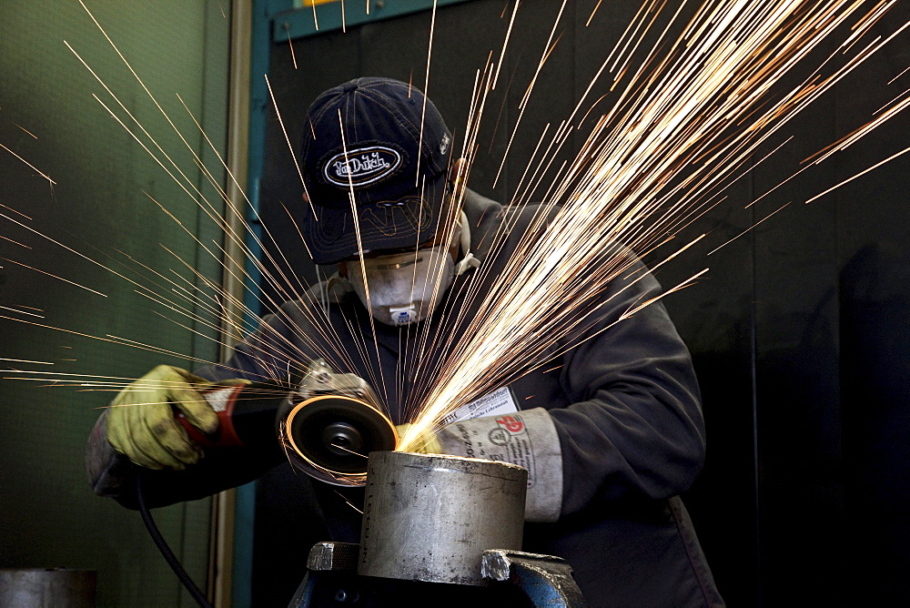 Apprentice grinding with an angle grinder in the welding workshop during a welding course of the School of the Chamber of Small Industries and Skilled Trades, Duesseldorf, North Rhine-Westphalia, Germany, Europe