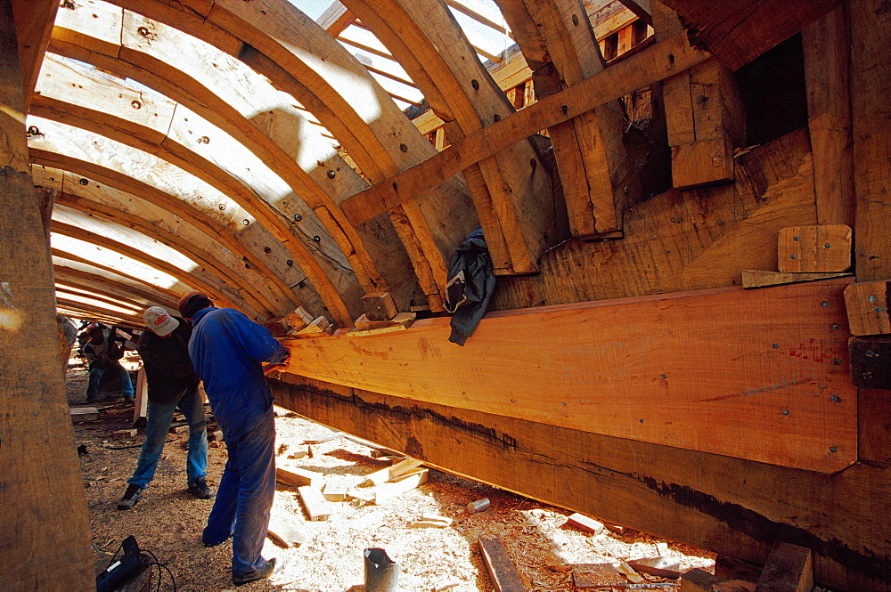 Shipwright under the hull of a trawler in the shipyard of Essaouira, Morocco, North Africa