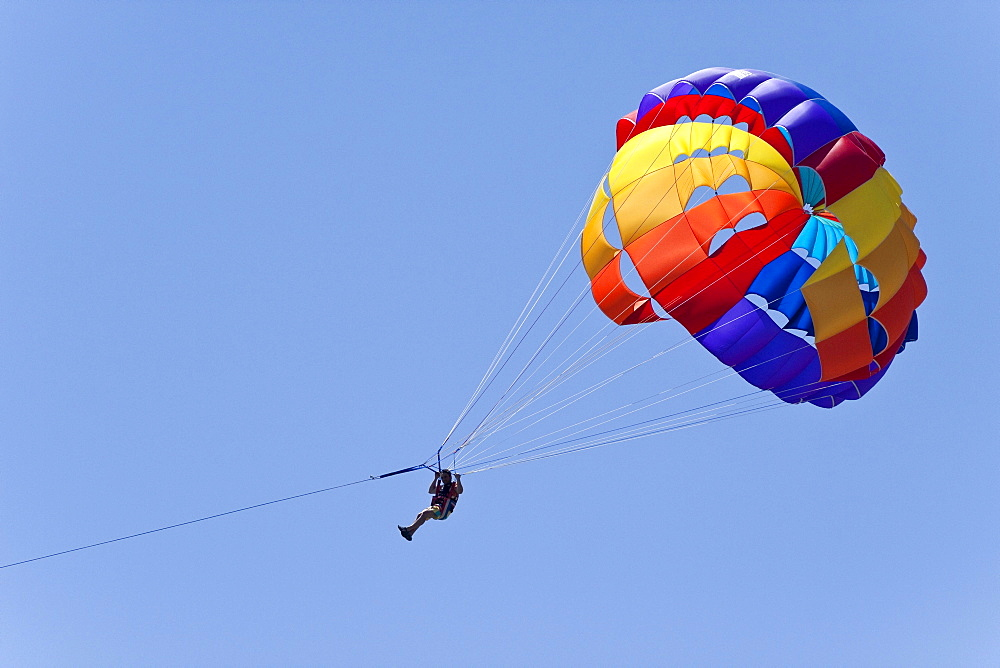 Man hanging from a paraglider high in the air, coast near Coral Bay, Cyprus, Europe