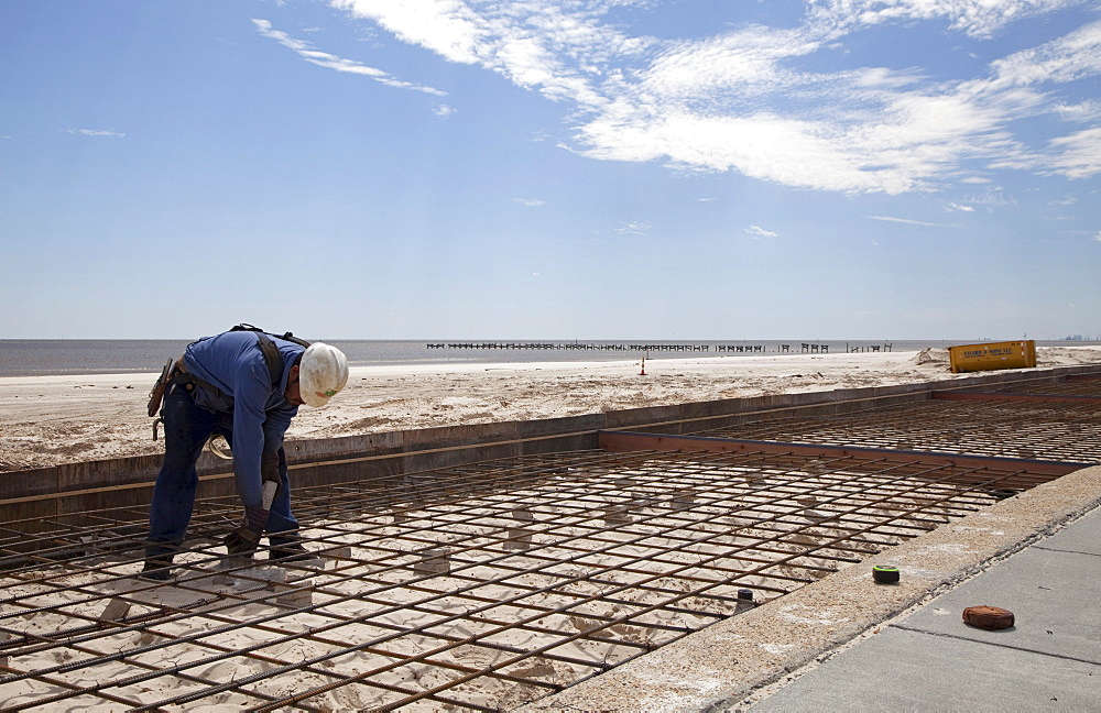 Workers construct a concrete boardwalk along the Gulf of Mexico to replace the boardwalk that was washed away by Hurricane Katrina, Biloxi, Mississippi, USA, Biloxi, Mississippi, USA