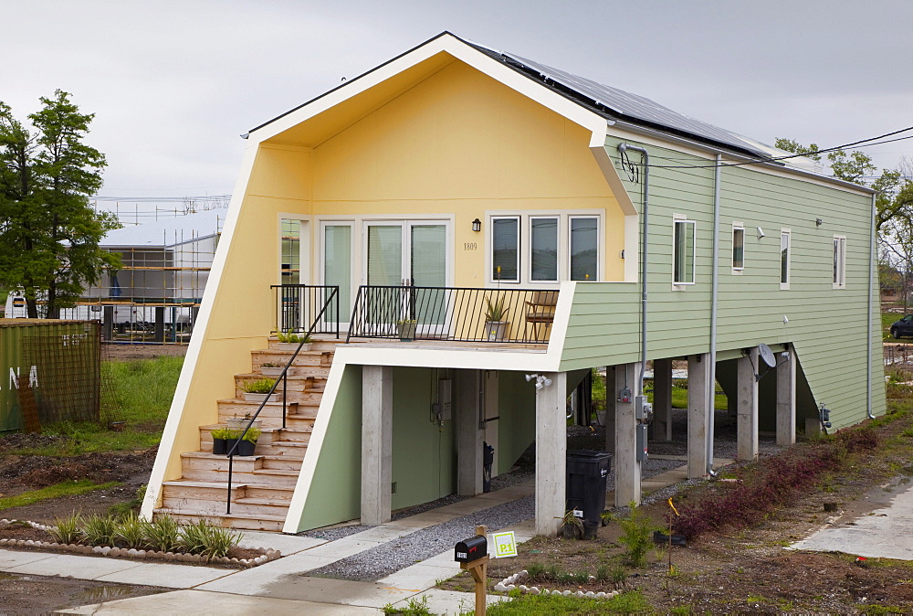 New homes built by Brad Pitt's Make It Right organization in the lower ninth ward which was devastated by Hurricane Katrina; the homes are all elevated and use energy-saving technology and eye-catching design, New Orleans, Louisiana, USA