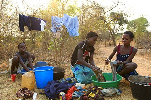 Teenagers washing clothes, washing square, African village Sambona, Southern Province, Republic of Zambia, Africa