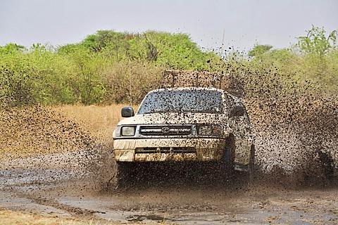 Four-wheel drive car driving through mud and water, Moremi National Park, Moremi Wildlife Reserve, Okavango Delta, Botswana, Africa