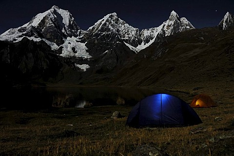 Tents glowing in the dark at Laguna Carhuacocha, from left, Yerupacha, Yerupacha Chico, and Jirishanca behind, Cordillera Huayhuash, Peru, South America