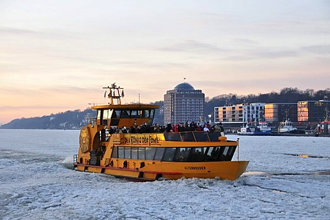 A fully occupied HADAG harbour ferry navigating the ice at the Port of Hamburg, Hamburg, Germany, Europe