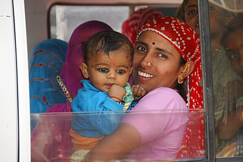 Indian woman holding a child in a fully occupied car, near Jodhpur, Rajasthan, North India, Asia