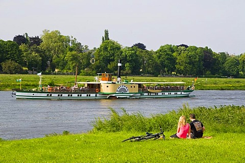 Couple on the shore of the river Elbe, paddle wheel steamer, Dresden, Saxony, Germany