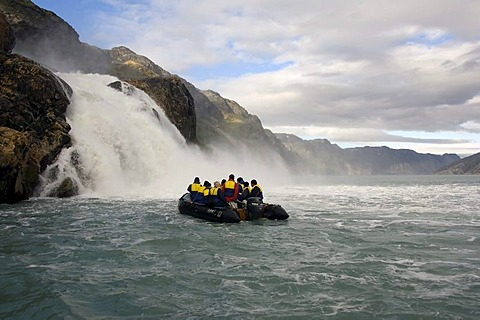 Zodiac with tourists approaching a waterfall, Arsuk Fjord, Greenland, Denmark